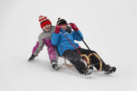 sledging: Two little girl in winter activity, sledging on wooden sledge downhill. Concept of winter activity enjoyed by children.