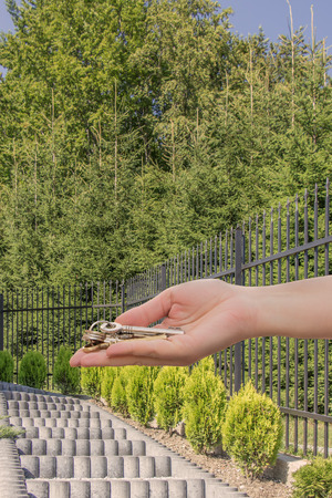 Woman hand offering keys in front of stairs to a home. Concept of optimistic future.