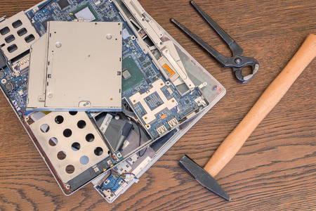 unskilled: Bad computer repair, broken old computer or laptop with hammer and pliers. Stock Photo