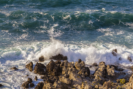 turbulent: Stormy turbulent sea, waves hitting rocks at the coast.