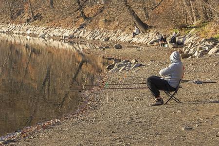 angler: Recreational angler, fisherman on the bank of the small pond.