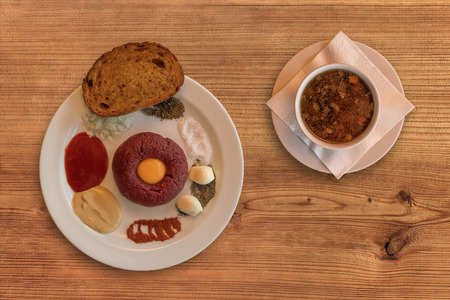 pyre: Flat lay of raw beef . Tasty Steak tartare. Classic steak tartare on rustic wooden table with a beef broth. Ingredients: Raw beef meat, salt, pepper, onion, caraway, mustard, tomato pyre, egg, garlic, toast or fried bread.