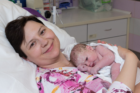 immediately: Happy mature woman, mother, with newborn baby immediately after delivery. Stock Photo