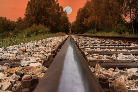 Railway line, trail or track going through landscape at sunset or dawn. Red sky with big evening sun.