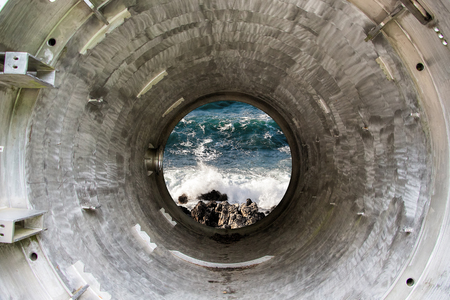 Deep iron tunnel or tube toward the sea, industrial view.
