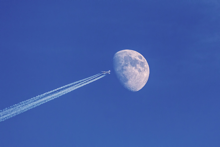 Modern jet plane with moon on blue sky as background, making illusion of space shuttle flying to the moon.