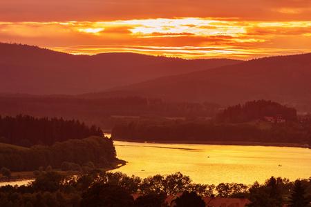 Bunte idyllische Sonnenuntergangslandschaft am See Lipno, im tschechischen Gebirge Sumava, im Böhmischen Wald oder im Böhmerwald, im Bayerischen Wald oder im Böhmischen Wald Standard-Bild - 104890771