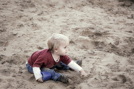 Happy baby girl, toddler, playing with sand on a playground. Standard-Bild