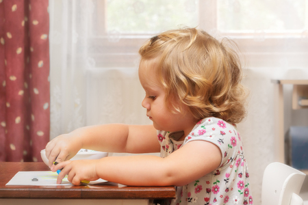 Soft portrait of two years blond kid, girl painting on the paper. Family life.