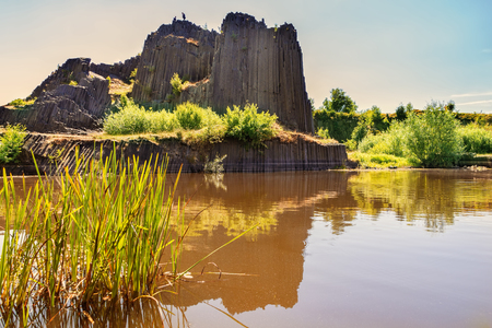 Rock of basalt with reflection on water lake. Famous landscape landmark called Panska skala at Kamenicky Senov at north of Czech Republic, 150 km north of Prague.