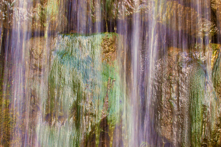 Abstract background image of waterfall flowing over green rocks, close-up.