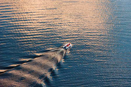 Aerial view of a small boat on wide blue water surface in evening sun. Diagonal composition suitable background.