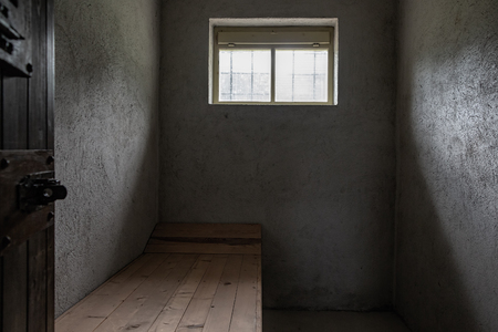 Small prison concrete cell with one small window and one wooden pallet.