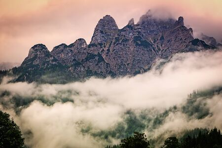 Rocky mountain ridge in Austrian Alps in the evening, dramatic foggy landscape. Standard-Bild