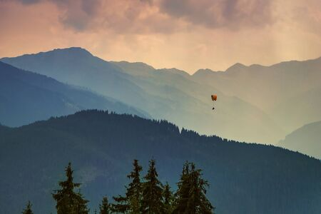 Moody picture of evening mountain ridges, Austrian alps, with a small paraglider on a horizon. Standard-Bild