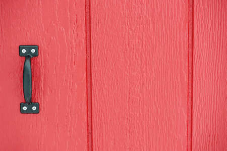Rustic red barn door background with black handle photo