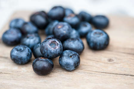 flavorful: Blueberries on wooden table; focus on single blueberry (Shallow DOF)