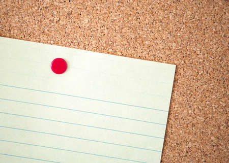 looseleaf: Blank yellow paper notepad with red tack on cork board background (Shallow DOF)