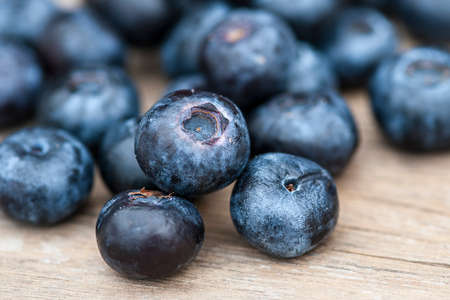 Blueberries on wooden table; focus on single blueberry (Shallow DOF) photo