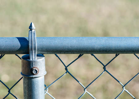 chainlink fence: Steel chain-link fence with green lawn background (Shallow DOF) Stock Photo