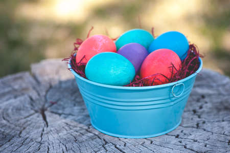 log basket: Vibrant Easter egg in metal tin with a wooden background; focus on the front egg (Shallow DOF)