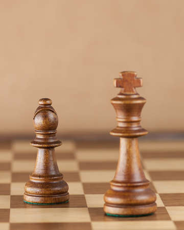 outwit: Chess pieces and game board background; focus on bishop (Shallow DOF)