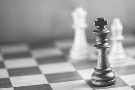 battle plan: Chess pieces and game board background, focus on king, black and white, shallow DOF