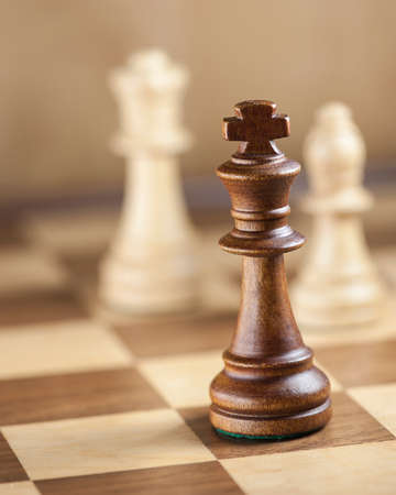 chess pieces: Chess pieces on game board background focus on the king shallow DOF Stock Photo