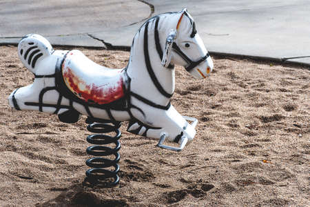 kiddie: Closeup view of antique rocking horse toy on a playground