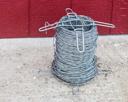 fencing wire: Closeup view of barbless wire spool with red barn door background shallow DOF