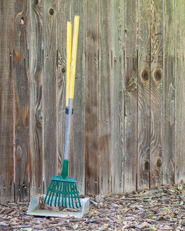 Small green and yellow gardening rake against wooden fence background. photo
