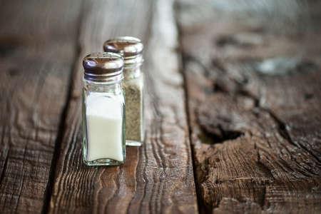 sal: Vista de la macro de sal y pimienta agitador par en la mesa de madera rústica DOF bajo