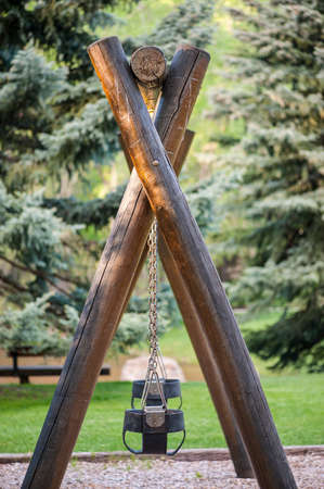 swing set: Vintage log timber swing set with two empty chain-link black swings, shallow DOF