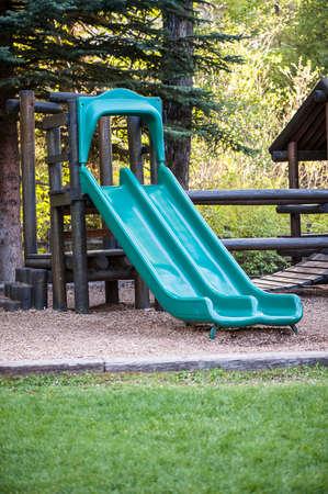 Two green slides on rustic mountain playground shallow DOF photo