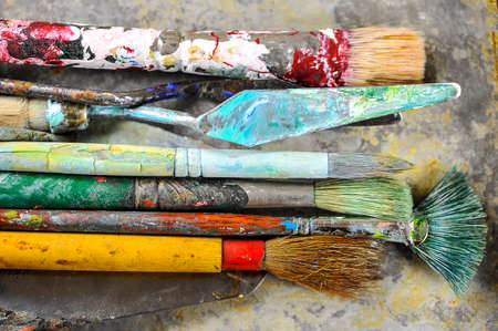 paint palette: Closeup view of dirty paint brushes on aluminum tray shallow DOF