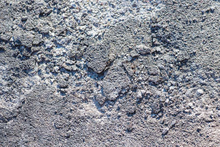 rupture: Macro view of a shattered gray concrete and stone background shallow DOF