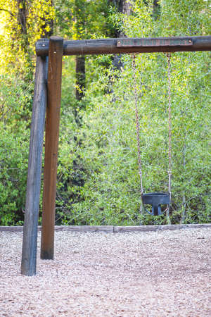 swing set: Vintage log timber swing set with empty chain-link black swing, focus on park sign, shallow DOF Stock Photo