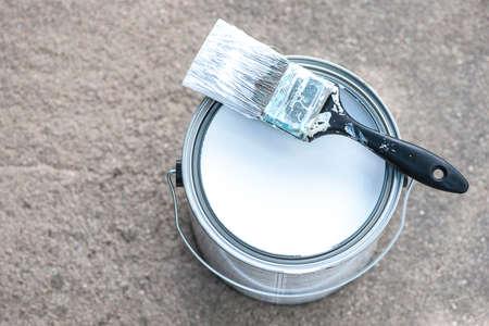 brocha de pintura: Vista de primer plano de la pintura de aluminio puede en concreto con pintura blanca y pincel sucio, DOF bajo