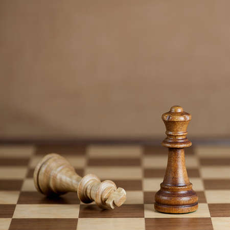 failed strategy: Chess pieces and game board background, focus on queen, shallow DOF Stock Photo