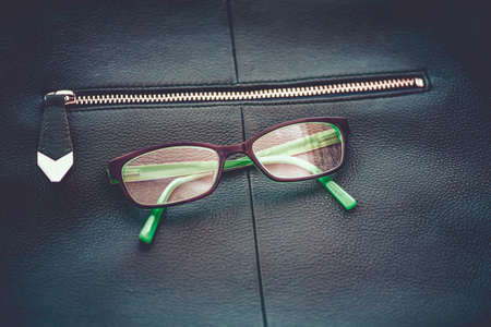 ojo verde: Macro view of green leather bag with gold zipper and green eye glasses, shallow DOF Foto de archivo