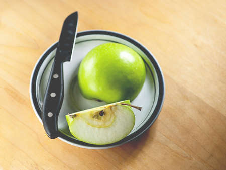 paring: Macro view of sliced green apple on rustic wooden cutting board with black paring knife, shallow DOF