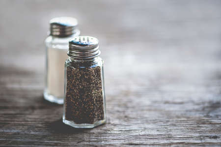 shaker: Macro view of salt and pepper shakers on rustic wooden table; shallow DOF