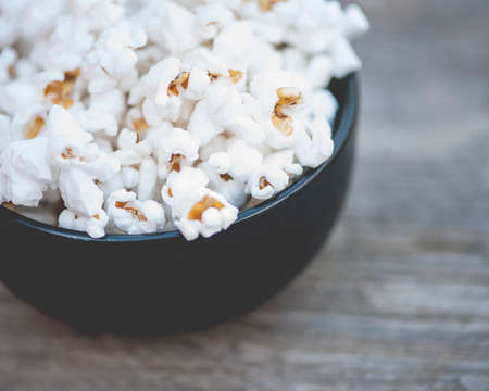 popcorn kernel: Close-up view of a bowl of white popcorn on rustic, wooden table, shallow DOF