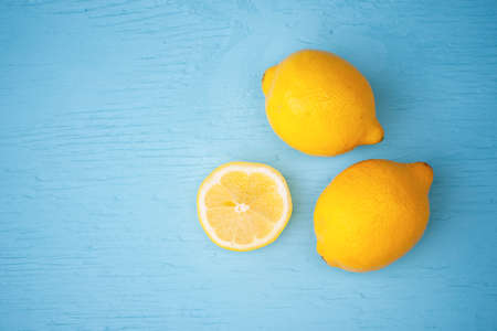 lemon: Macro view of vibrant, yellow lemon slice and two whole lemons on rustic, wooden teal table background, shallow DOF Stock Photo