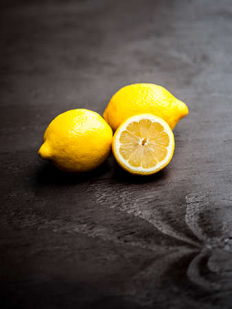 slice: Macro view of vibrant, yellow lemon slice and two whole lemons on dark brown, rustic, wooden table, shallow DOF