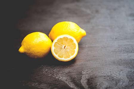 lemons: Macro view of vibrant, yellow lemon slice and two whole lemons on dark brown, rustic, wooden table, shallow DOF