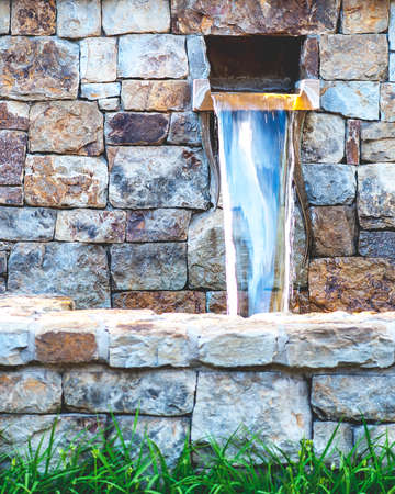 water feature: Close-up view of artistic water fountain with vibrant stone wall, shallow DOF