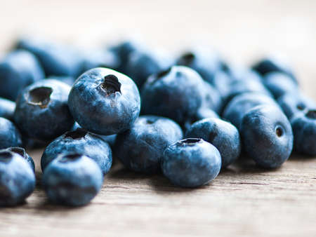 black currants: Blueberries on wooden table; focus on single blueberry Shallow DOF