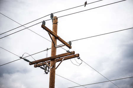 telephone pole: Close-up view of telephone pole and wire with cloudy, stormy sky background, shallow DOF