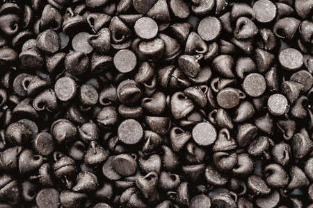morsel: Macro view of dark chocolate chip morsel background, shallow DOF Stock Photo